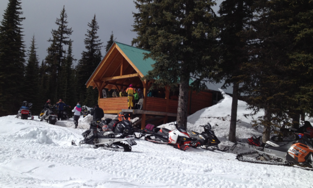 Ingersol Cabin is wooden, large and has a green roof. An assemblage of snowmobiles are parked up front.