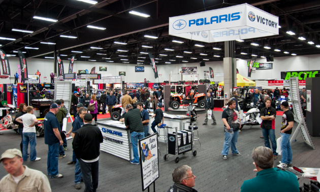 A busy show floor full of people, booths and vehicles at the Edmonton Expo Centre.