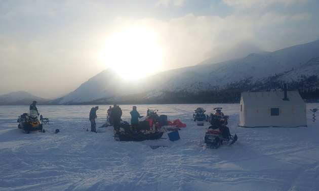 Snowmobilers gather around a warm-up shelter next to Alligator Lake.