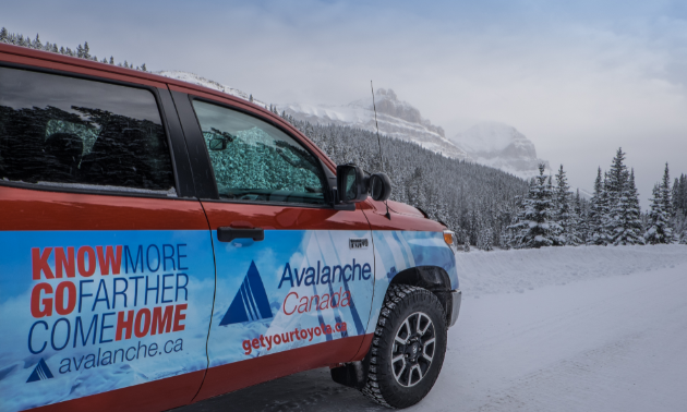 A red, white and blue truck with Avalanche Canada written on the side, parked in the mountains.