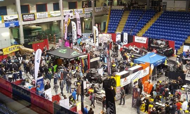 A hockey arena full of snowmobile vendors and customers.