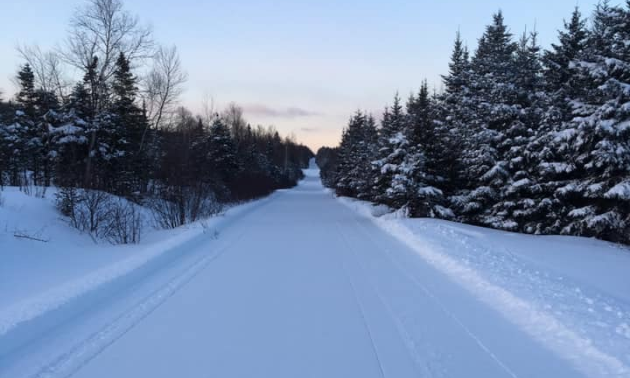 A long, wide trail is groomed for snowmobiles to ride on.