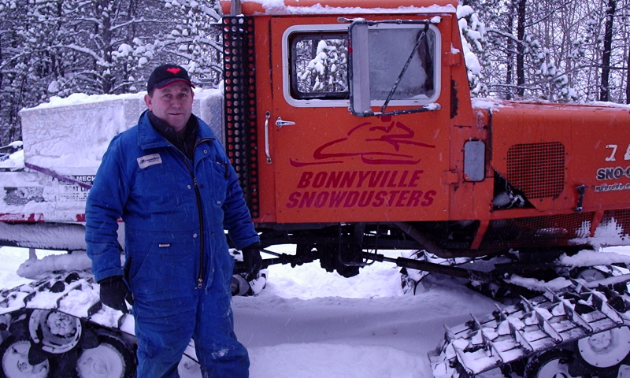 Angus Ross stands next to a snowmobile groomer.