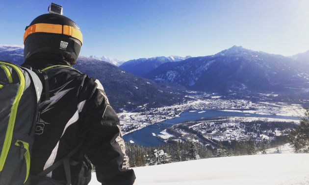 A snowmobiler looks down upon Revelstoke from a high location on Boulder Mountain.