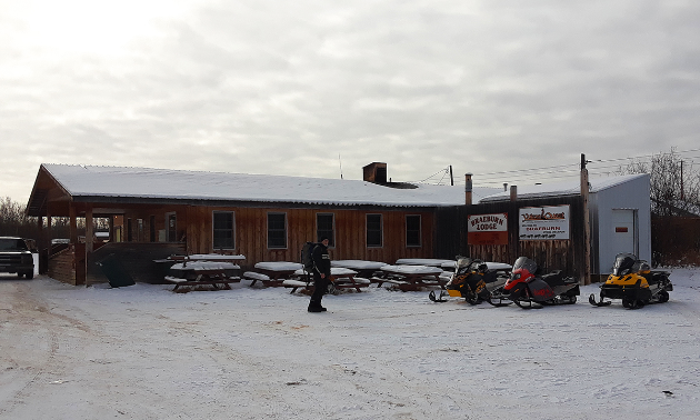 The Braeburn Lodge is brown with a few snowmobiles parked up front.