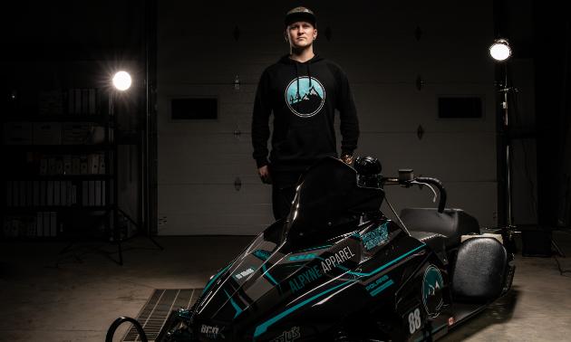 Brennan Boxall stands behind his black snowmobile, a 2014 Wahl Bros Champ.