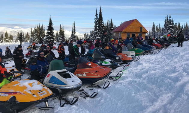 A long row of vintage snowmobiles is lined up in front of a warm-up cabin on a snowy mountain.