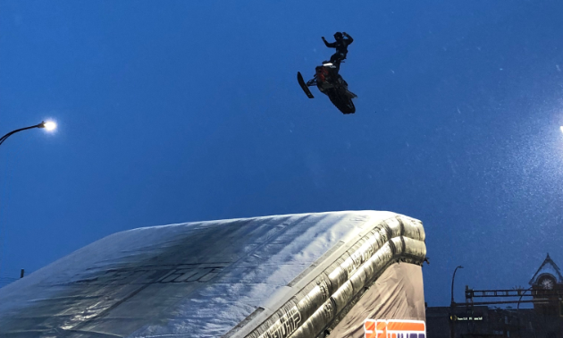 A snowmobiler gets major air before landing on a ramp.