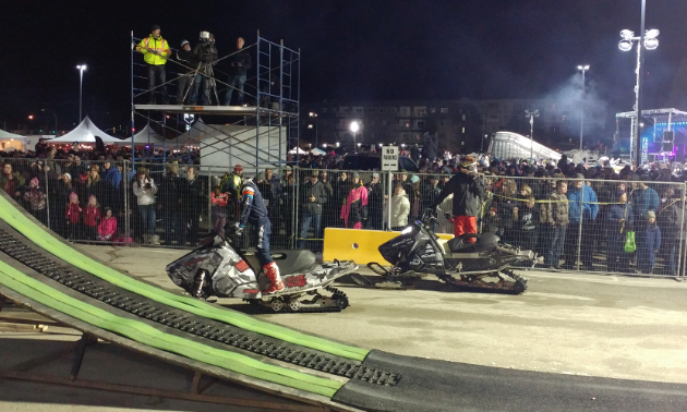 Two snowmobilers stand on their sleds in a fenced-in area.