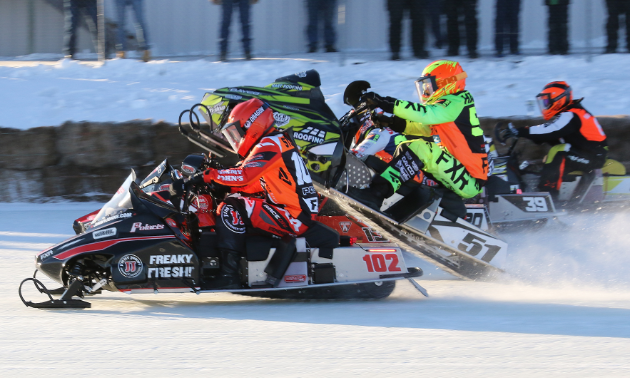 A side view of several snowmobile racers that are neck and neck with each other.