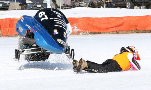 A snowmobiler is thrown from her sled as it skips into the air.