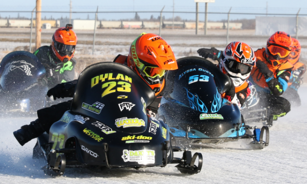 Five children race snowmobiles around a track.