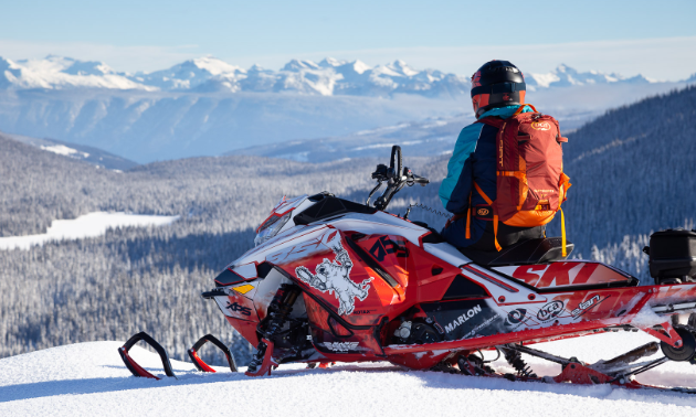 David Norona sits on his snowmobile, looking into the mountains in the distance.