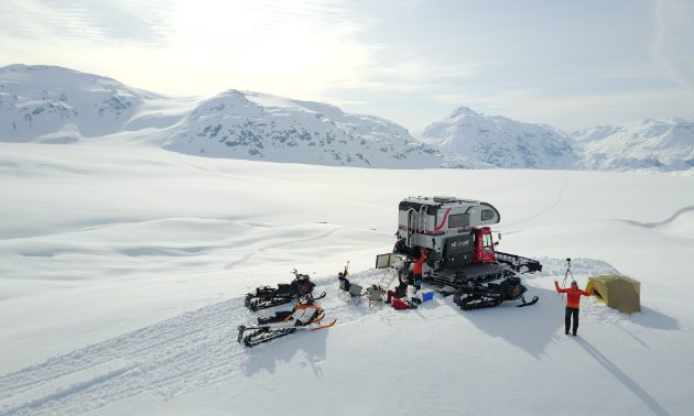 A groomer and two snowmobiles are parked on a snowy, isolated plateau.
