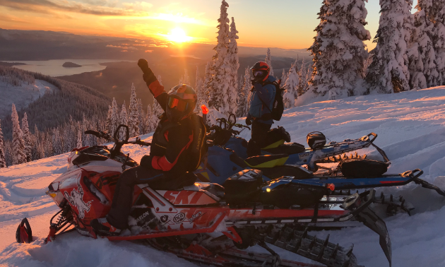 David Norona fist-pumps on his snowmobile as the sun sets in the distance.