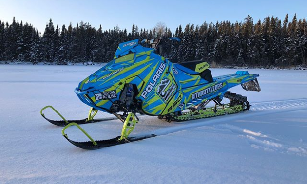 A blue and neon green snowmobile on the snow with the woods in the background.