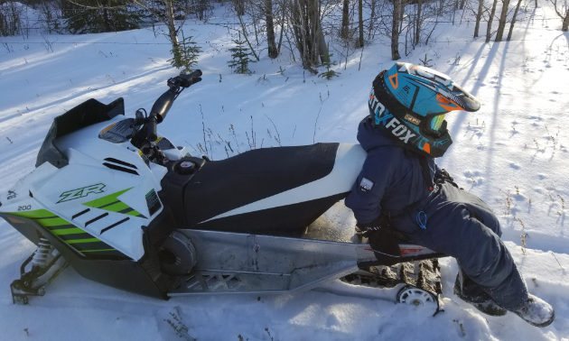 A young boy sits on the track of his white, black and green 2018 Arctic Cat ZR.