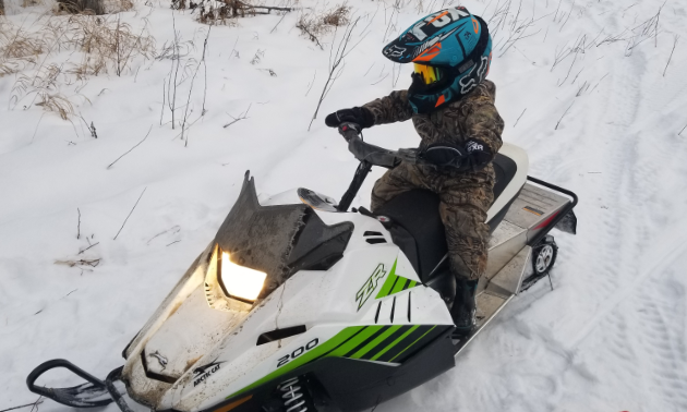 A young boy rides his white, black and green 2018 Arctic Cat ZR.