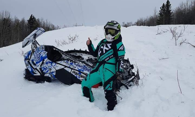 A woman in a turquoise jumpsuit gives a thumbs up next to her overturned blue and white snowmobile.