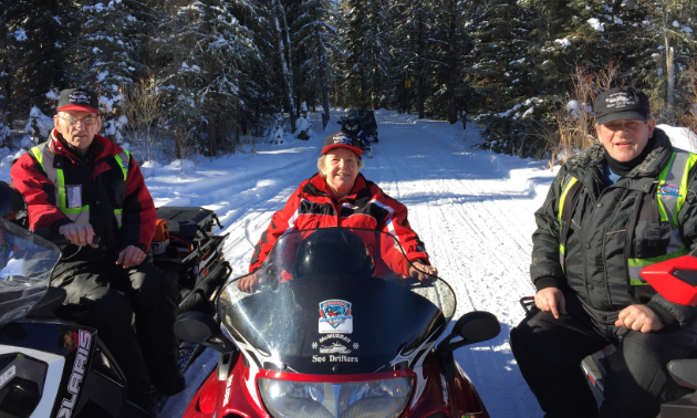 (L to R) Elburne, Freda and Barry Bean sit on their sleds in Fort McMurray.