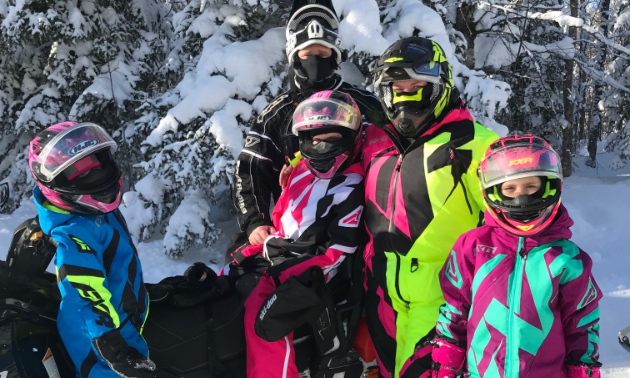 Husband Craig (black suit) and wife Shelly (pink and yellow suit) pose with their three daughters Raya (blue and yellow suit), Kerri (pink and white suit) and Brooke Plett (purple and mint suit).