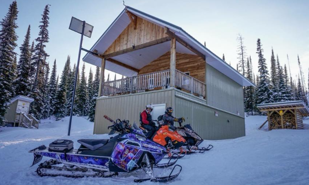 Two snowmobilers park in front of the Rolling Hills Cabin in Fernie.