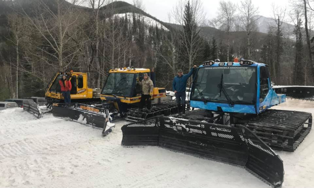 Three snowcat groomers line up next to each other on top of snow.