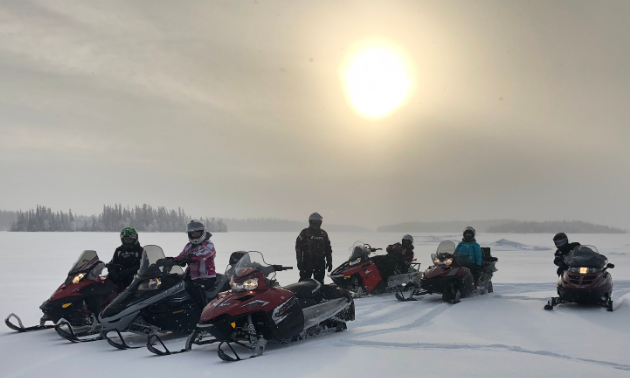 Six snowmobilers stop on a flat snowy field near Flin Flon Manitoba with the sun trying to shine through the clouds in the background.