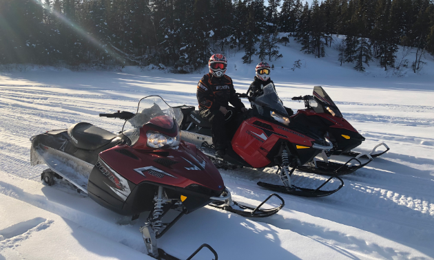 Three stationary snowmobiles, two with people sitting on them, on a flat trail with trees in the background.