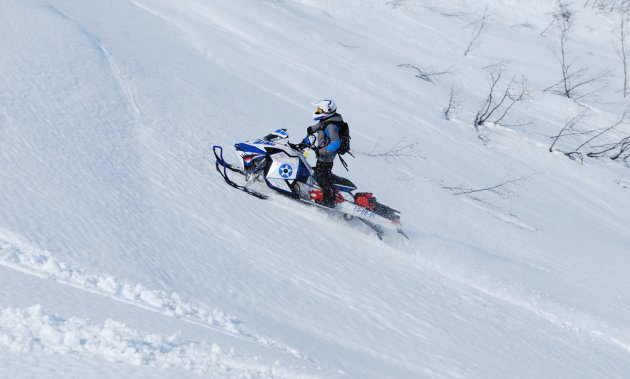 A snowmobiler climbs up the side of a mountain.