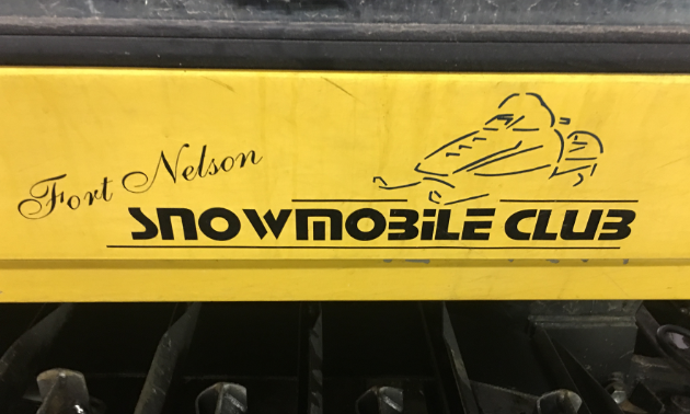 A yellow sign of the Fort Nelson Snowmobile Club