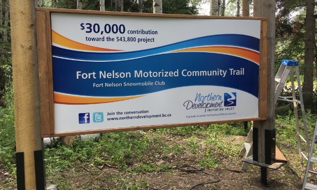 A government sign explaining how the Fort Nelson Snowmobile Club made its upgrades to its trail system.