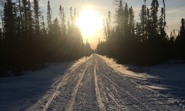 The sunrise comes up over the snowmobile trail.