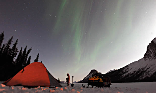 A tent, snowmobile and northern lights in the mountainous Fort St. John area.
