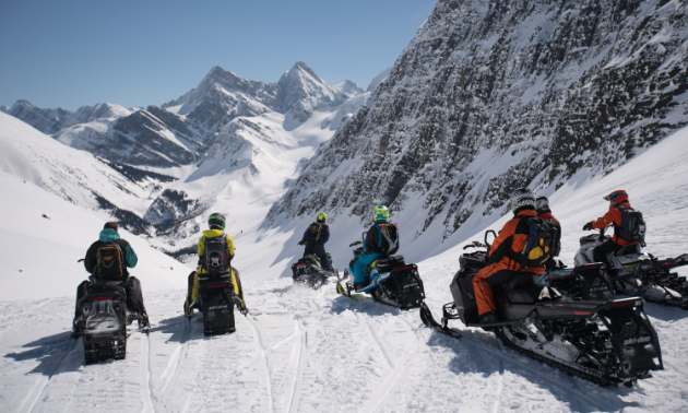 Six snowmobilers drive into a snowy valley.