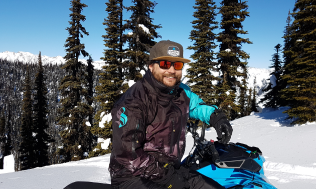 Curtis Pawliuk smiles on his blue snowmobile on a snowy, tree-filled hill.