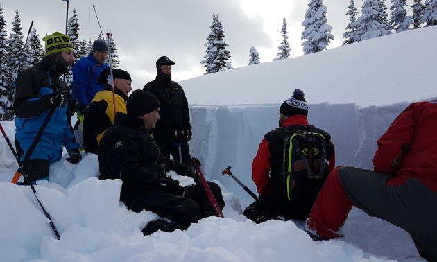 Curtis Pawliuk instructs a group of students how to work in a snow profile.