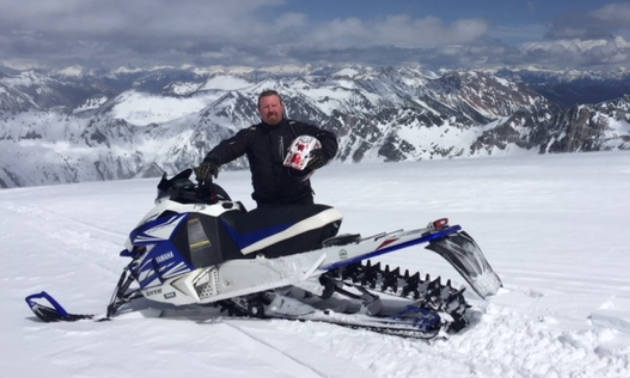 Gary Prosser poses with his snowmobile on a mountain in Radium Hot Springs.