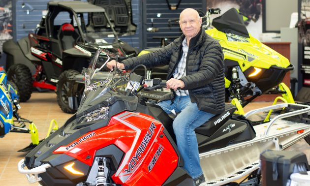 Gerry Dolezsar sits on a snowmobile in a store.