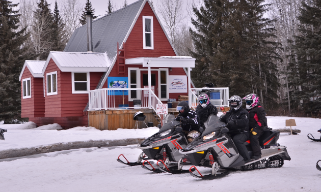 Two snowmobiles carrying three riders prepare to embark on adventure in front of a red cabin in the woods.