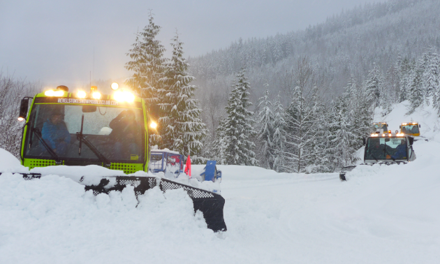 Several snowcat groomers plow trails on a snowy mountain.