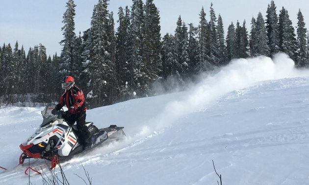 A plume of white smoke puffs up from a snowmobile as it makes its way down a hill.