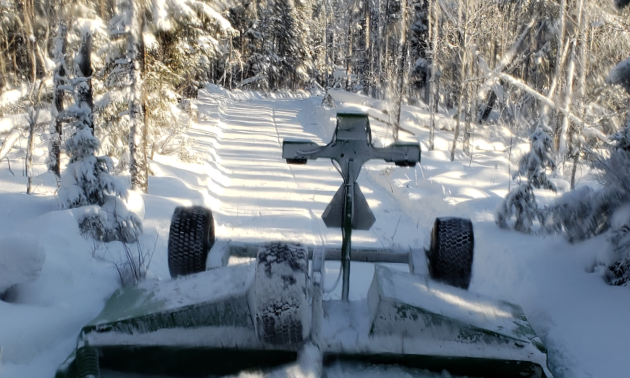 A drag smooths snow along a snowmobile trail.
