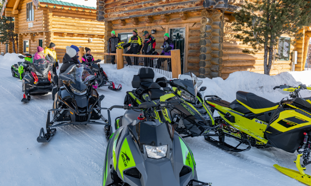Snowmobiles are parked in front of a log cabin. People gather on the porch to visit with each other.