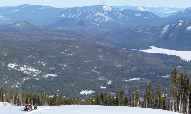 Snowmobilers ascend Hendrix Mountain and look into the valley below.