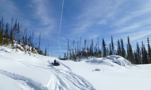 A snowmobiler parks on a trail under a blue sky.