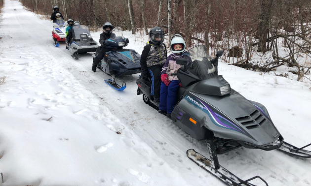 Kids ride vintage snowmobiles on a trail in Manitoba.