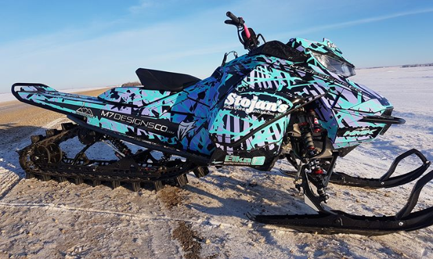 A turquoise and purple snowmobile.