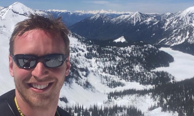 Josh Salzmann has short brown hair and is smiling while wearing sunglasses. The South Purcell Mountains are in the background.