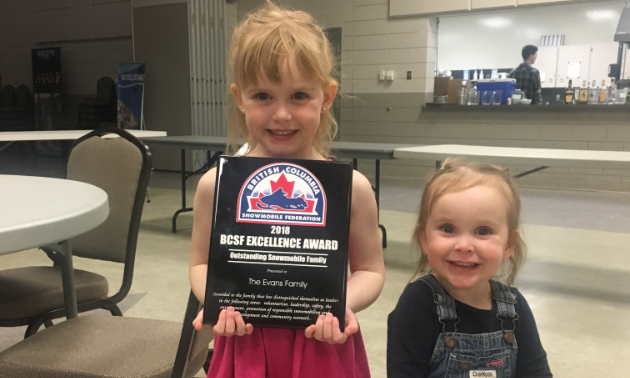 The Evans family won the Excellence Award for Outstanding Snowmobile Family by the British Columbia Snowmobile Federation. Five-year-old Paisley and two-year-old Brooklyn are happy to show off the award.